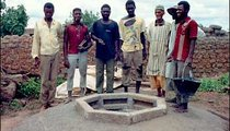 A repair team gathers around a well project. The concrete has recently been laid on the mound surrounding the well. Solo Kelema, on the far right, is a metal worker, and built the brick molds used for the concrete bricks.