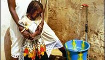 Badiane and her daughter, Soukeina, fill a bucket for bathing at the family's new faucet.
