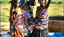 Colorfully dressed girls and women are ready to carry their water from the well back to their homes.