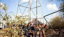 Local children play around the water tower. Notice the barbed wire and the fencing to ward off elephants.