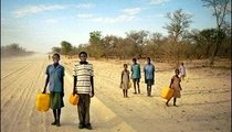 Children carry water containers to school that they will fill on the way home. They live four kilometers away from a tap. Notice the road—the government plows and waters it during the dry season to prevent it from getting too dry, dusty, and dangerous to drive on.
