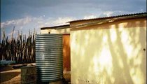 This Namibian family has a water tank and tap on their homestead with a catchment system to collect roof runoff during the rainy season. The family also fetches water in large containers that they carry home in a car. The water is then dumped into this tank.