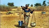 Dade Mahchi undertakes her daily walk home carrying two heavy pots of water and a baby on her back.