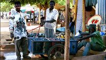 Men fill their carts with large cans of water that they will deliver and sell to villagers.