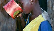 Ablay Sarr takes a drink from an old tomato-paste can that everyone in the compound shares.