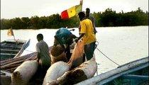 Men work together to load sacks of millet onto boats.