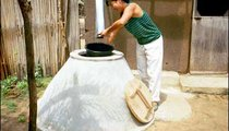 I'm fetching water from my cistern built by the local mason. During the rainy season, water is plentiful for me.