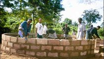 Village men work together to build an enclosure for one of their village pumps that was funded by the nongovernmental organization SEFI.