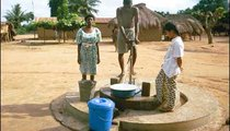 Mawuli pumps the water with his foot while Jeanette (left) and I look on. This village water pump was repaired recently.
