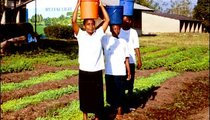 Girls from the Girls' Secondary School in Korogwe carry buckets of water to the garden.