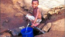 A young boy fills his morning bucket from a faucet in Old Korogwe village.