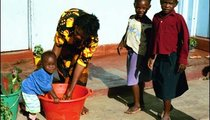 Deniso (left) is teaching her one-year-old child, Violet, how to wash her hands.