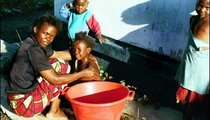 Bana Denne is bathing her daughter, while the boys wait their turn.